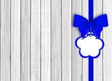 White wooden background with beautiful blue bow with tag Royalty Free Stock Photo