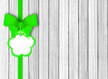 White wooden background with beautiful green bow with tag Royalty Free Stock Image