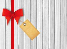 White wooden background with beautiful red bow and tag Royalty Free Stock Photo