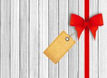 White wooden background with beautiful red bow and tag Stock Image