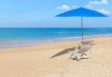 White wooden beach chair and blue parasol on tropical beach Stock Image