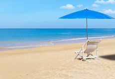 White wooden beach chair and blue parasol on tropical beach. In sunny day Royalty Free Stock Photos
