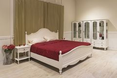 White wooden bed with dark red blanket and white pillows. The room Bridal Suite in an expensive hotel. A cozy bedroom. a chest of drawers, mezzanine, bede Stock Photography