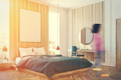 White and wooden bedroom, poster corner toned. Corner of a white and wooden bedroom interior with a wooden floor, a large window, a blue bed and two bedside Royalty Free Stock Photography