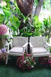 White wooden bench in a garden stock photography