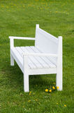White wooden bench on green grass Royalty Free Stock Photography