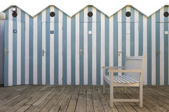 Bench with beach cabins background. White wooden bench near the seaside: beach cabins background royalty free stock photo