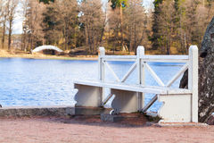 White wooden bench stands on lake coast Stock Images