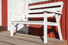 White wooden bench on terrace of red wooden house. White wooden bench stands on terrace of Scandinavian red wooden house Royalty Free Stock Photos