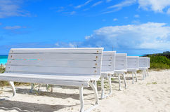 White wooden benches. At the white sandy beach in Cuba Stock Image