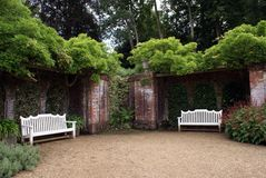 White wooden benches or seats in a walled garden. White wooden benches or seats on a gravel path in a walled garden Stock Images
