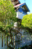 White wooden bird house on a picket fence post. House in the background. Port Townsend, WA Royalty Free Stock Images