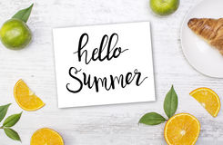 White wooden board with food and paper. Hello summer lettering. Royalty Free Stock Photos