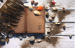 White wooden board with sand and shells, antique notebook. And pencil stock photography