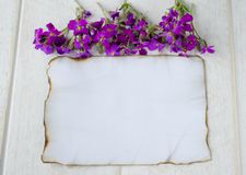 On white wooden boards, a white sheet of paper was burning on the edges, and purple flowers, leaving room for text royalty free stock image