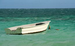 White Wooden Boat. A small white boat anchored in the ocean Royalty Free Stock Image