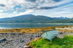 White wooden boat on the beach on Hakoya island, Norway stock photos