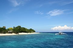 White wooden boat on deep blue sea and sky of Balicasag island snorkeling spot for coral reef, Panglao, Bohol, The Philippines