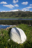 White wooden boat on the shore of the Norwegian lake in spring, snowly mountains on background Stock Photography