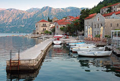 White wooden boats float moored in Perast Stock Photo