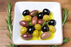 White wooden bowl with a variety of olives and rosemary in oil Royalty Free Stock Photos