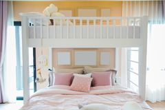 A white wooden bunk bed with a pink pillows and frames on wall i. N a children`s bedroom with warm light from a window Royalty Free Stock Photos