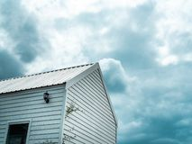 White wooden cabin against the cloud and blue sky background