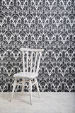 White wooden chair. Against vintage style wallpaper in studio Royalty Free Stock Images