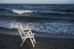 White wooden chair on the beach. Empty beach, sunset, cold weather and the sea. Stock Photos