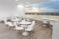 White wooden chair in dining room of modern office with windows. White wooden chairs in dining room of modern office with windows and city view Stock Images