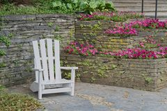White wooden chair for relaxing at stone wall with flowers in bloom. `Planten un Blomen` city garden in Hamburg, Germany royalty free stock photography