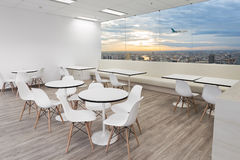 White wooden chairs in dining room of modern office with windows. And city views Stock Photo