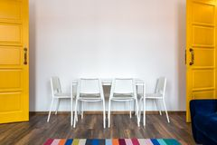 White wooden chairs with a table against the background of a white wall in the interior with yellow doors royalty free stock photos