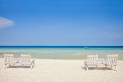 White wooden chairs on white sand beach Royalty Free Stock Image