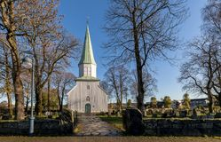 White wooden church seen from the side, trees, grass and blue sky in autumn, Kristiansand, Norway Stock Image