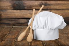 White cooks cap and wooden spoons on wooden table. White wooden cook cap cooks spoons color image stock photos