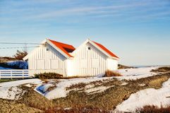 White wooden cottage with red roofs on coast Stock Image