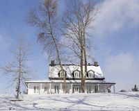 White wooden country house with snowy black roof in winter landscape royalty free stock photos