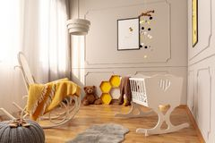 White cradle and rocking chair with cozy yellow blanket in bright grey toddler room stock image