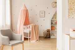Crib with canopy. White wooden crib with pastel pink canopy standing in bright newborn baby interior with grey chair and gold dots on the wall stock images