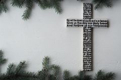 White wooden cross with the Lord`s prayer on the shabby wooden plank with fir tree branches background royalty free stock photos