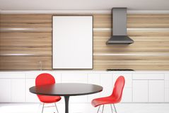 White and wooden dining room, red chairs close up. White and wooden dining room interior with a concrete floor, a black round table with two red chairs standing Royalty Free Stock Image