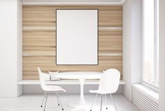 White and wooden dining room, table and poster. White and wooden dining room interior with a concrete floor, a round table with two white chairs standing near it Stock Photos