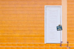 White wooden door and the orange wall with old rusty metalplate Stock Photos