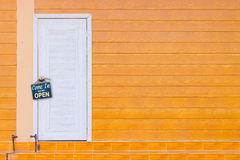 White wooden door and the orange wall with old rusty metalplate Stock Image