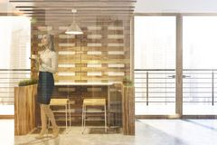 White and wooden eco bar interior, woman. White and wooden walls eco bar interior with loft windows and wooden tables and chairs. Flower beds. A front view. A Royalty Free Stock Images