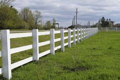 White wooden fence around the ranch. WhiteWhite wooden fence around the ranch. Wooden fence in the village stock photography