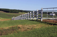 White wooden fence crossing a farm yard Stock Photo