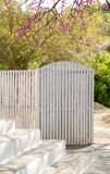 White wooden fence and dor open of the house outside extertior and blossomins pink tree in spring stock photo