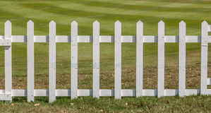 White wooden fence in farm field marks for land property. Stock Photography